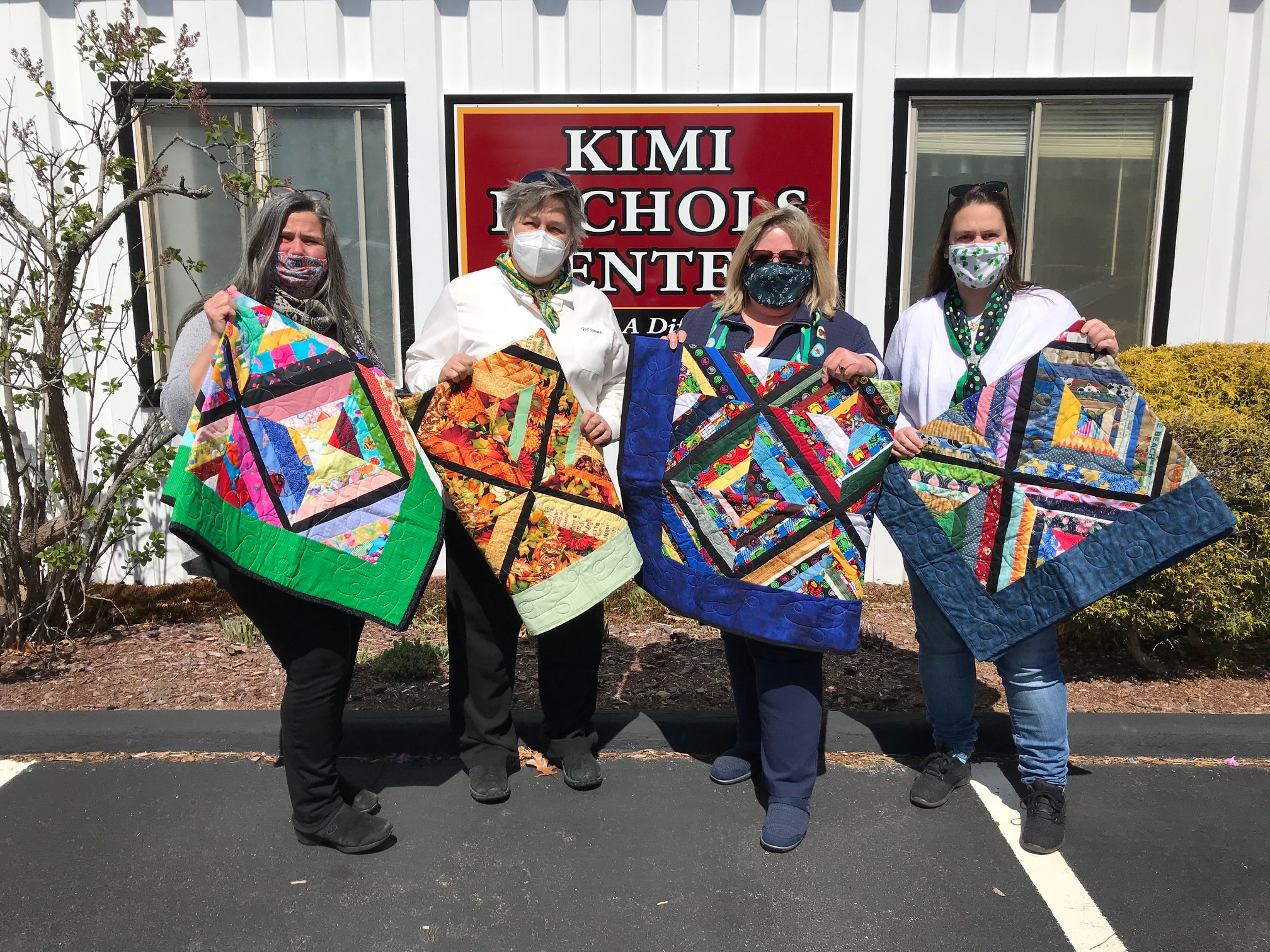 Kathy with Joanne, Deb, and Stephanie with the quilts donated by the Farnsworth Quilters of the Girl Scouts of the Green and White Mnts Alumni Association